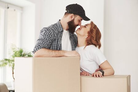Give me a kiss. Happy couple together in their new house. Conception of moving.