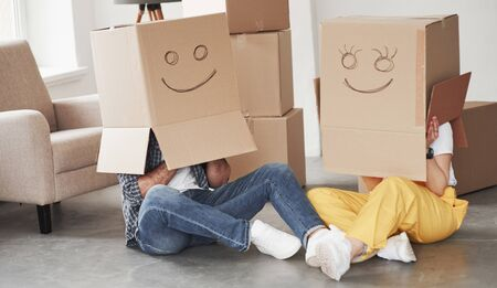 상자에 미소. 그들의 새 집에서 함께 행복 한 커플입니다. 이동의 개념입니다.