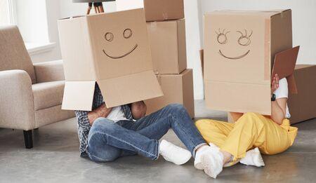 Lächeln auf Kisten. Glückliches Paar zusammen in ihrem neuen Haus. Konzeption des Umzugs.