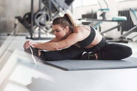 Thats nice stretch. Photo of gorgeous blonde woman in the gym at her weekend time.