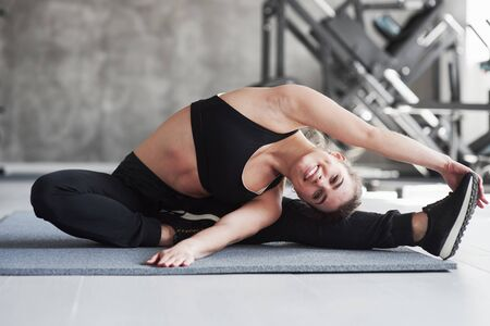Come do yoga with me. Photo of gorgeous blonde woman in the gym at her weekend time.