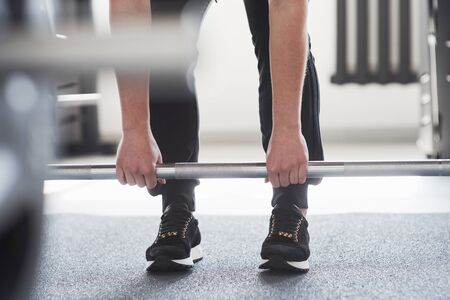 You can do it. Cropped photo of woman doing squatting with barbell in the gym.