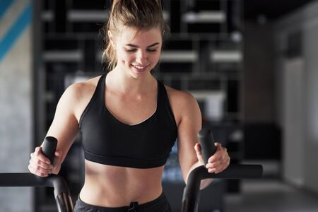 On bicycle. Photo of gorgeous blonde woman in the gym at her weekend time. Stock fotó