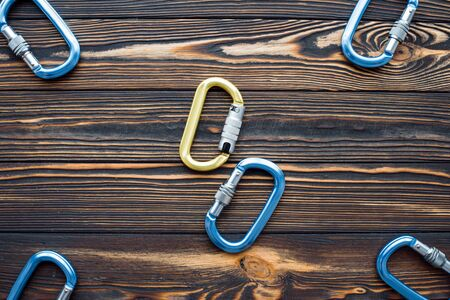Yellow and blue colored. Isolated photo of climbing equipment. Parts of carabiners lying on the wooden table.