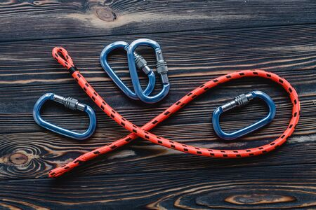 Conception of extreme sports. Isolated photo of climbing equipment. Part of carabiner lying on the wooden table.