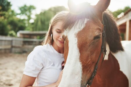 Peace and quiet. Happy woman with her horse on the ranch at daytime.