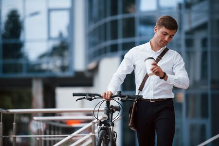 Im not will late. Businessman in formal clothes with black bicycle is in the city. 写真素材