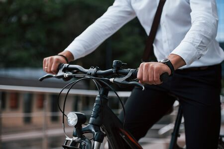Close up view. Businessman in formal clothes with black bicycle is in the city.