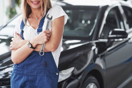 Standing against black automobile. Nice blonde woman repairer is on her work. Indoors at car shop. Stock fotó - 135502132