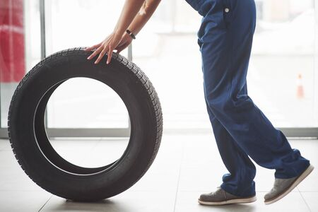 Cropped photo. Woman walks with brand new wheel to the car. Conception of repair. Stock fotó - 135502477