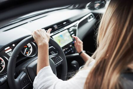 Using map on display. Close up view of woman's hands in the beautiful modern black colored car. Reklamní fotografie - 135502194