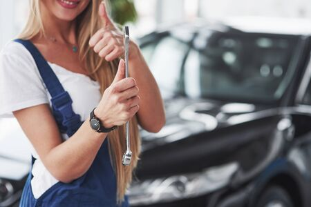Shows thumb up and holds wrench in other hand. Nice blonde woman repairer is on her work. Indoors at car shop. Stock fotó - 135502150