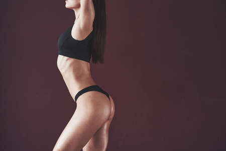 Showing left side. Pretty young woman with nice fitness body shape posing in the room. Reklamní fotografie
