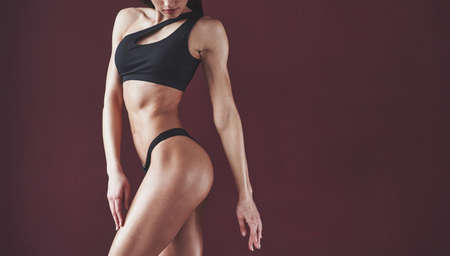 Healthy lifestyle. Pretty young woman with nice fitness body shape posing in the room. Reklamní fotografie