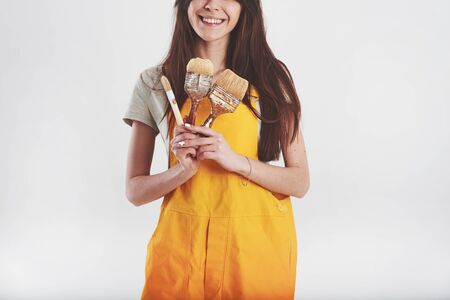Pretty brunette in yellow uniform stands against white background in the studio. Stock fotó