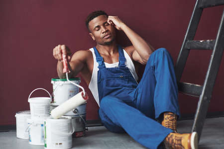 Tired and sleepy. Young african american worker in blue uniform have a break on his job. Banco de Imagens