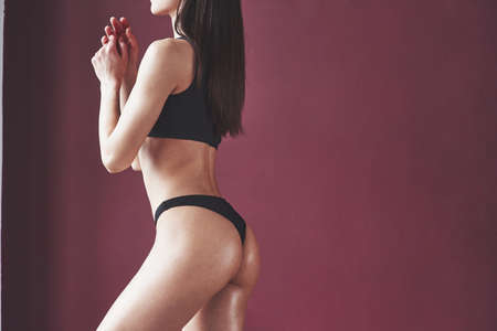 Against burgundy wall. Pretty young woman with nice fitness body shape posing in the room. Reklamní fotografie