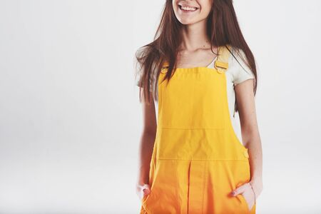 Smiling for the camera. Brunette woman in yellow uniform stands against white background in the studio. Reklamní fotografie - 135503253