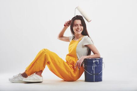 Make it easy. Brunette woman in yellow uniform sits against white background in the studio. Banco de Imagens