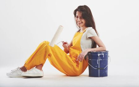 Easy and fun. Brunette woman in yellow uniform sits against white background in the studio.