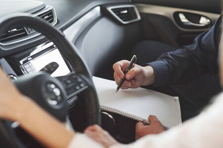 Writing important information. Assistant manager giving advices and help to the customer in automobile salon.