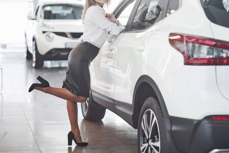 Pretty woman in black skirt posing near brand new car in automobile salon. Banque d'images - 135503476