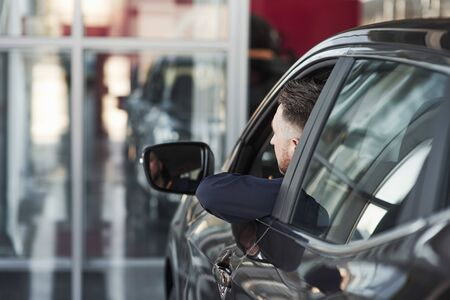 Looks in the side mirror. Man in official clothes trying his new car in automobile salon. Banque d'images - 135503447