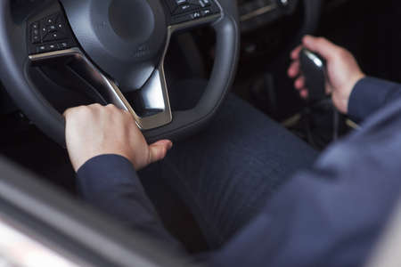 Gear shifting. Man in official clothes trying his new car in automobile salon. Banque d'images - 151143683