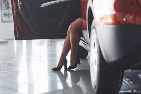On high heels. Beautiful blonde girl sitting in the new car with modern black interior. Banque d'images