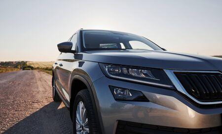 Moderne nieuwe auto geparkeerd op de zijweg op het platteland overdag. Stockfoto