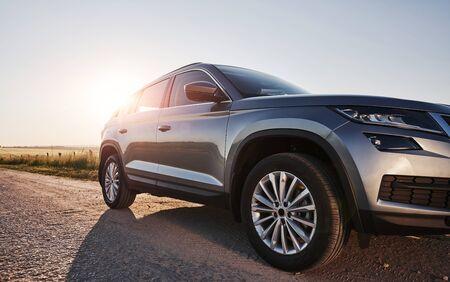 La lumière du soleil passe sur l'automobile. Nouvelle voiture moderne garée sur la route secondaire à la campagne pendant la journée. Banque d'images