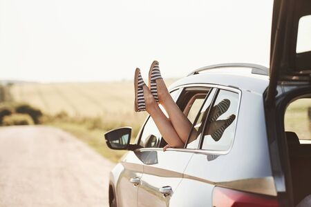 In black and white striped slippers. Girl puts out her legs on the automobile window at countryside.