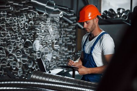Wrtining in notepad. Man in uniform works on the production. Industrial modern technology.