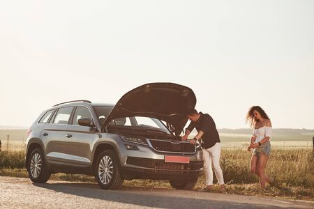 Everything will be okay. Man repairs car of girl with curly hair. Mechanical assistance. 免版税图像