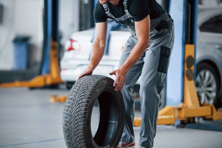 It's easier to walk that way. Mechanic holds a tire at the repair garage. Replacement of winter and summer tires.