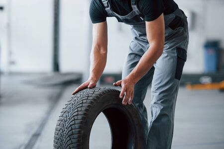 Photo in motion. Mechanic holds a tire at the repair garage. Replacement of winter and summer tires.