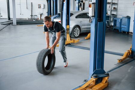In working clothes. Mechanic holds a tire at the repair garage. Replacement of winter and summer tires.