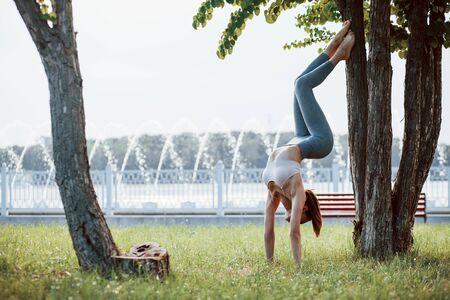 Foto en movimiento. Mujer joven con tipo de cuerpo delgado hace ejercicios en el parque.