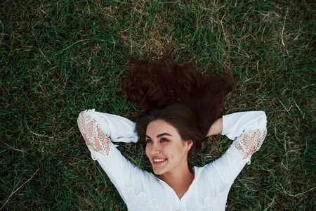 Feels freedom. Girl lying down on the green grass and have a rest.