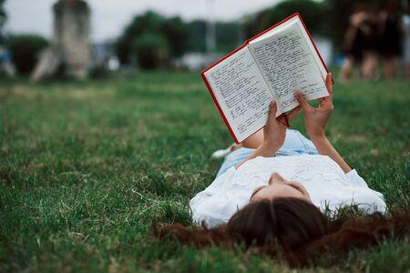 La persona adulta lee el bloc de notas. Chica acostada sobre la hierba verde y descansar.