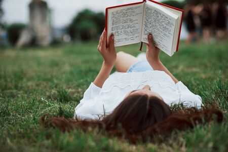 Book with red cover. Girl lying down on the green grass and have a rest.