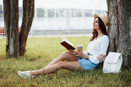 Attractive smiling girl. Young woman have weekend and sits in the park at daytime.