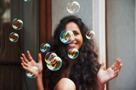 Cute girl plays with bubbles like a child. Beautiful woman with curly black hair have good time in the city at daytime.
