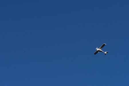 Biplane flying high in the blue sky at sunny day. Speed and energy.