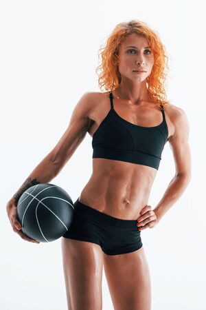 With black soccer ball. Redhead female bodybuilder is in the studio on white background.