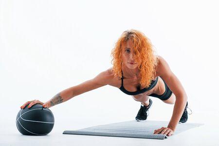 With black soccer ball. Redhead female bodybuilder is in the studio on white background. Foto de archivo