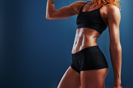 Cropped photo. Redhead female bodybuilder is in the studio on blue background.