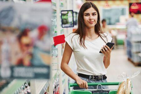 Nowoczesne centrum handlowe. Kobieta shopper w ubraniach casual na rynku poszukuje produktów.