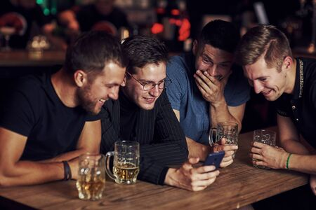 Funny content on smartphone. Three friends resting in the pub with beer in hands. Having conversation.