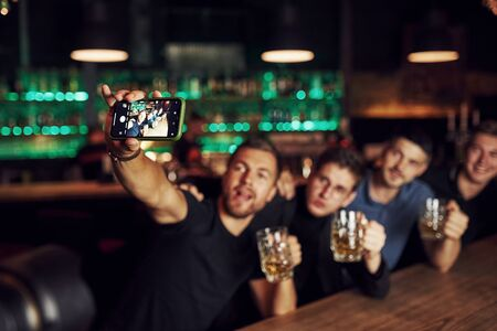 Making a selfie. Three friends resting in the pub with beer in hands. Having conversation.
